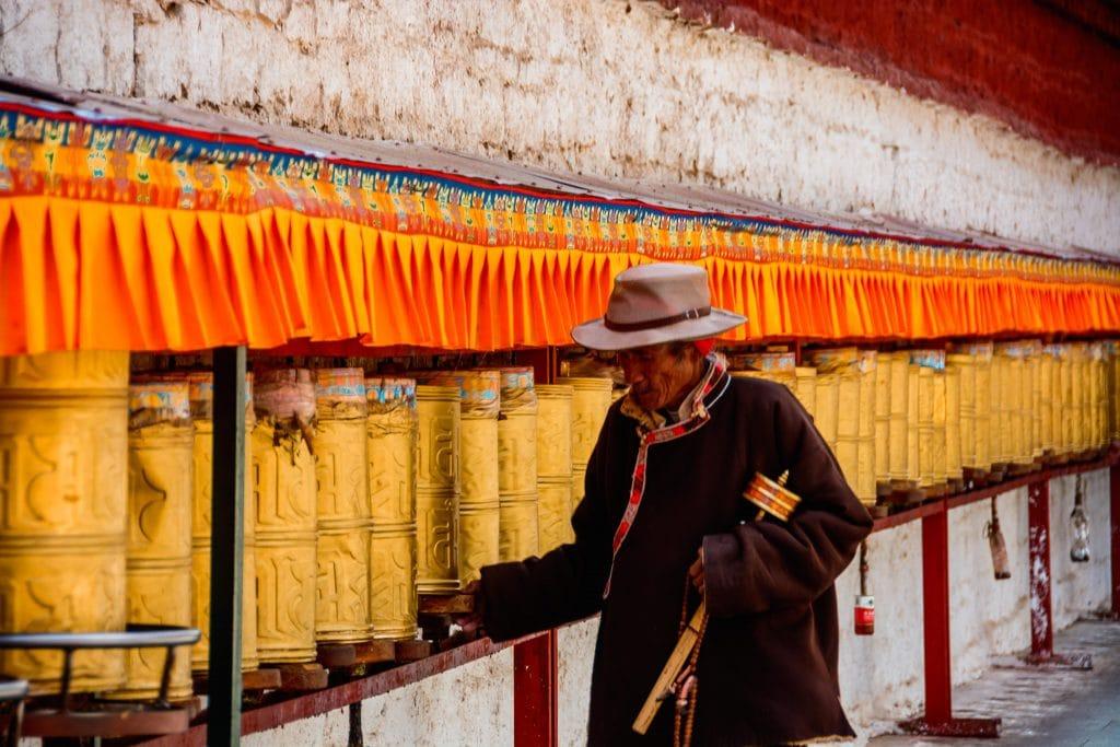 Tibetan man rotating prayer wheels walking kora around Potala Palace