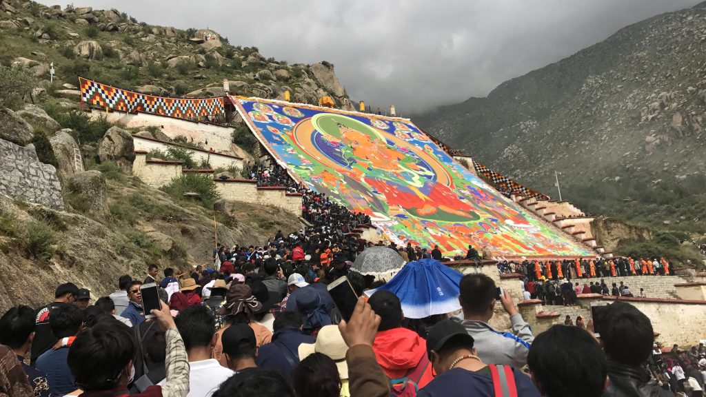 People are walking towards and underneath Thangka to receive blessing during Shoton