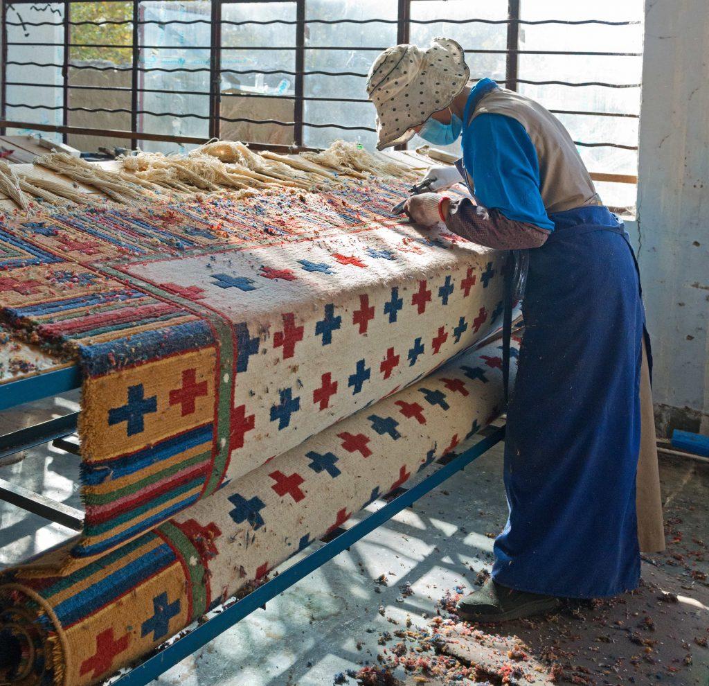 Tibetan woman working on traditional Tibetan rug